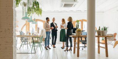 Four women standing around corporate kitchen