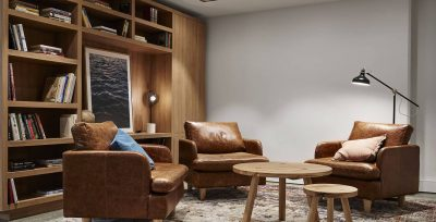 three leather chairs and bookshelf with lamp